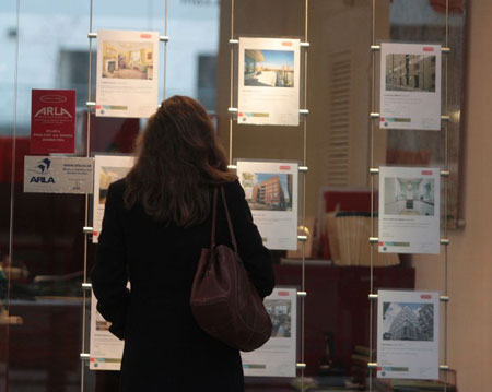 Woman looks in estate agents window